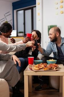 Grupo diversificado de trabalhadores se divertindo após o trabalho no escritório