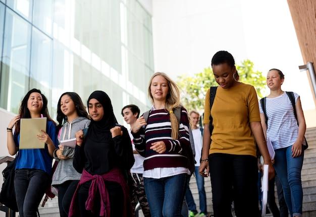Grupo diverso de estudantes caminhando na escola