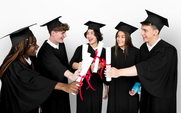 Grupo diverso de estudantes segurando o diploma