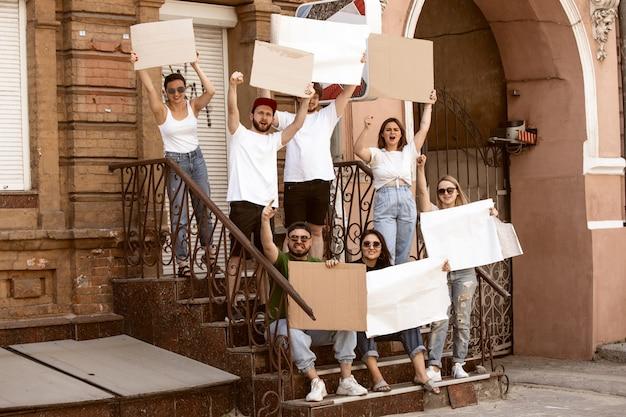 Grupo diverso de pessoas que protestam com sinais em branco. protesto contra os direitos humanos, abuso de liberdade, questões sociais