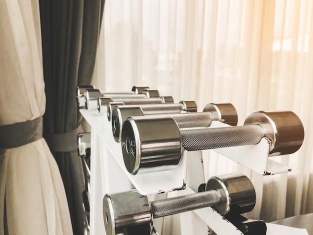 Grupo do close up de pesos diferentes dos pesos para exercitar os músculos do braço no gym.