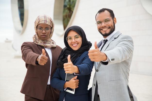 Grupo empresarial multicultural posando e fazendo como gesto