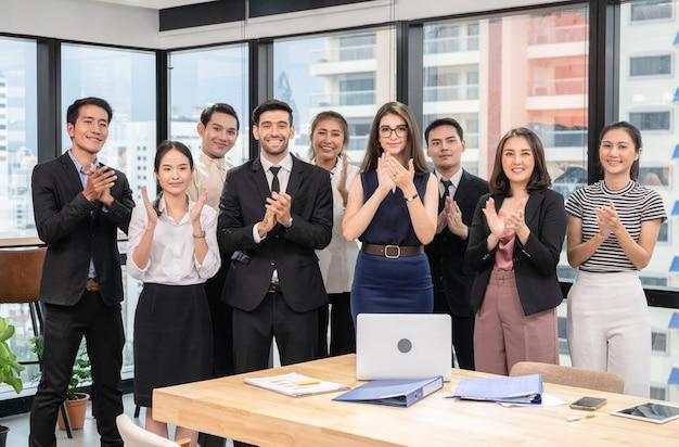 Grupo empresarial multiétnico batendo palmas de sucesso após seminário de negócios em escritório moderno
