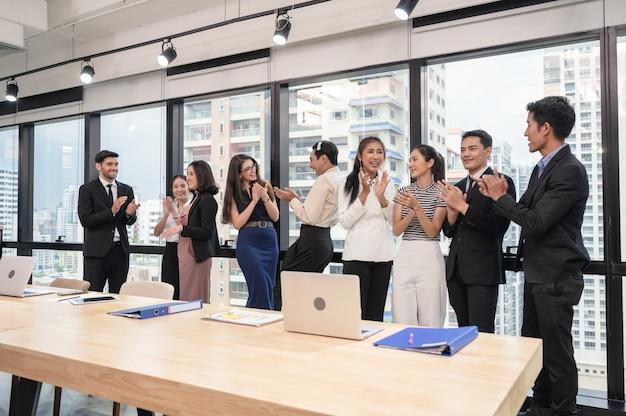 Grupo empresarial multiétnico batendo palmas de sucesso após seminário de negócios no escritório