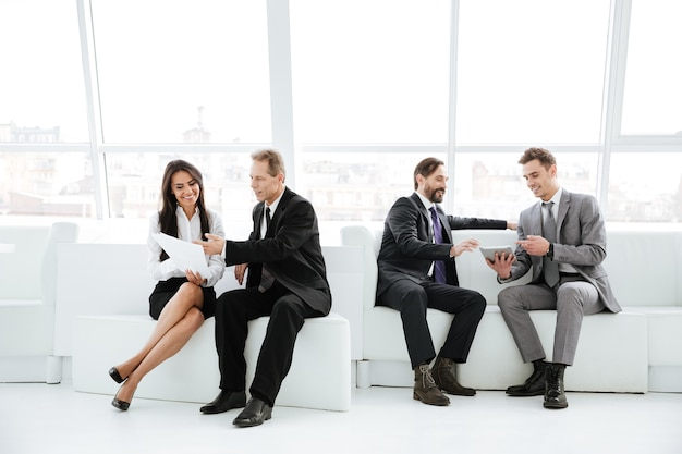 Grupo empresarial sentado no escritório no sofá perto da janela.