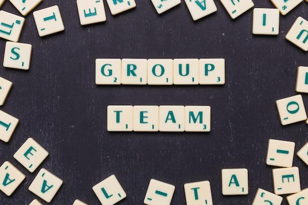 Grupo equipe scrabble letras sobre fundo preto