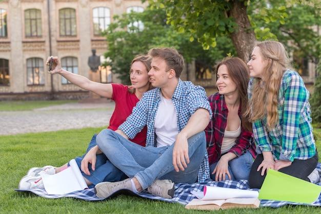 Grupo estudantes, sentando, perto, árvore