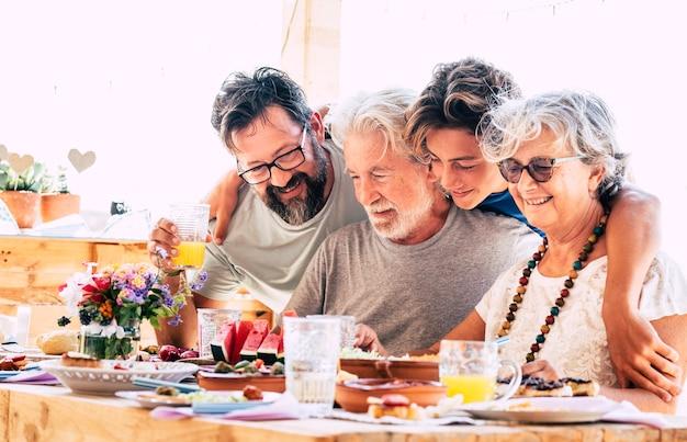 Grupo familiar de pessoas com gerações mistas se divertem juntos no jantar