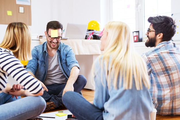 Grupo feliz brincalhão jovem de pessoas sentadas no chão do escritório enquanto joga adivinha a nota.