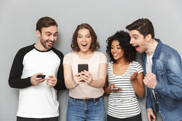 Grupo feliz chocado de amigos usando telefones celulares, olhando de lado.
