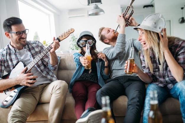 Grupo feliz de amigos divertidos e alegres tocando instrumentos e festejando