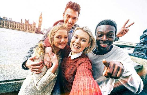 Grupo feliz de amigos multirraciais tirando uma selfie em londres, em uma viagem pela europa