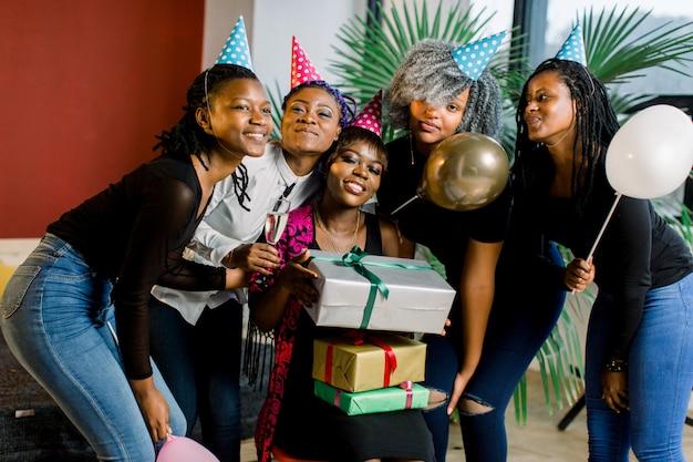 Grupo feliz meninas africanas com presentes coloridos e balões nas mãos, olhando para a câmera e sorrindo
