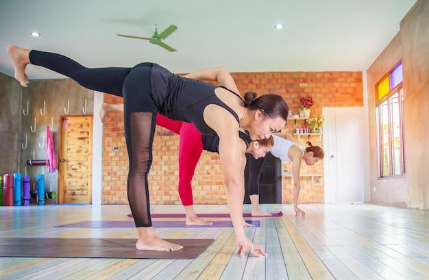 Grupo fêmea asiático da aptidão que faz a pose da ioga do namaste na fileira na classe da ioga. foco seletivo