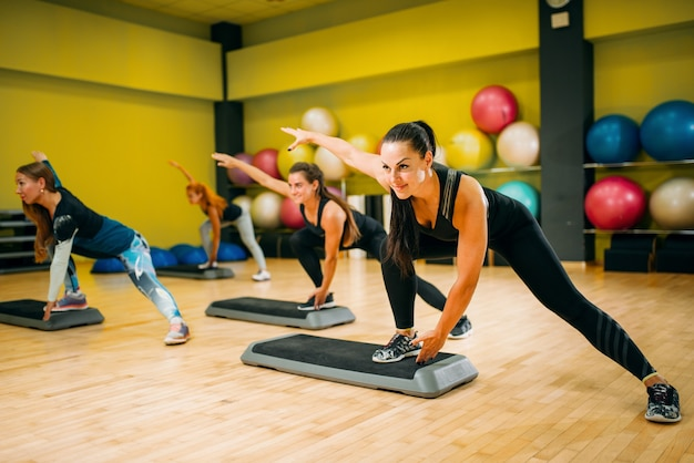 Grupo feminino em treino aeróbico de step