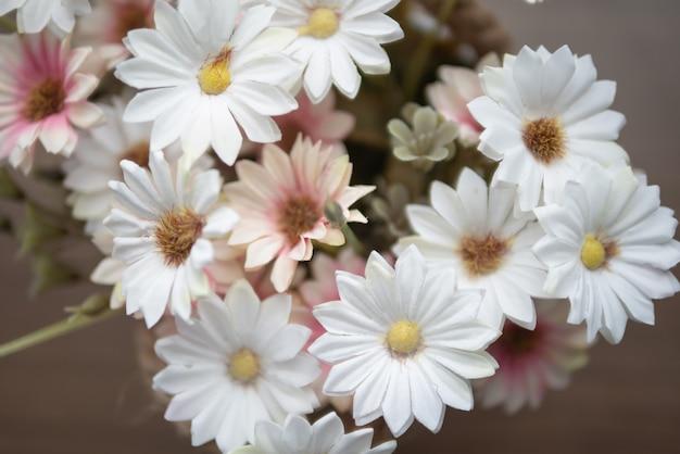 Grupo flores brancas e rosa na mesa de madeira