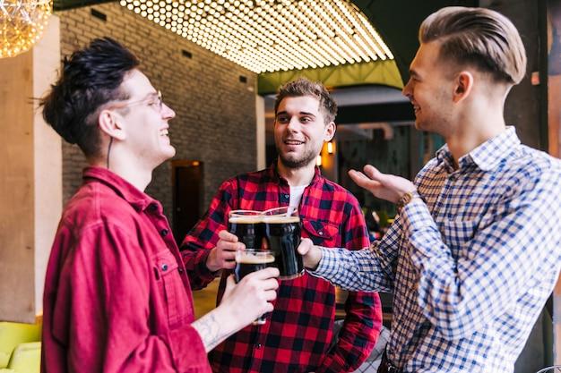 Grupo homens, brindar, a, copos cerveja, em, barra, restaurante