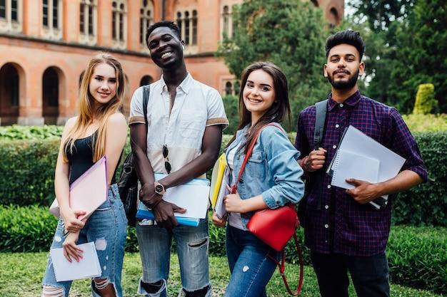 Grupo inteligente de alunos sorridentes caminhando juntos, caminhando perto da faculdade e se abraçando.