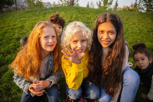 Grupo inter-racial de crianças, meninas e meninos brincando juntos no parque no dia de verão