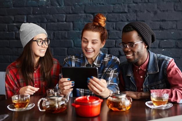 Grupo inter-racial de três descolados usando touch pad em um café