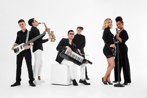 Grupo internacional de músicos em uma parede branca, guitarrista, baterista, solistas, saxofonista. copie o espaço, relkama para instrumentos musicais.
