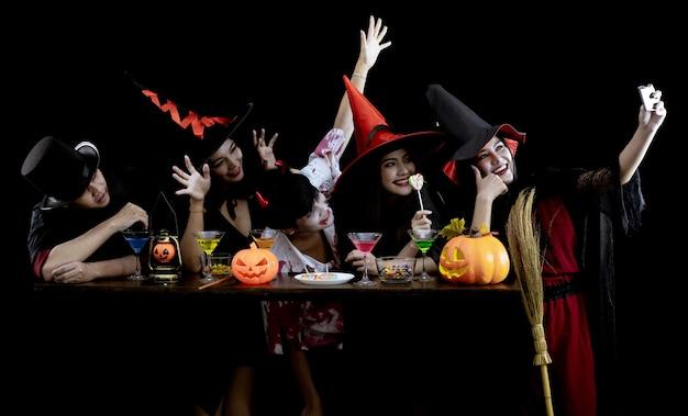 Grupo jovem asiático em traje comemora festa de halloween e selfie na parede preta ... fantasma fantasma, mal do grupo adolescente tailandês com diversão.