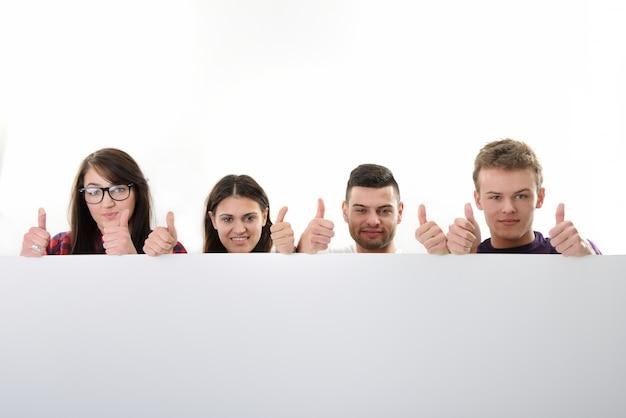 Grupo jovem com polegares atrás de um banner