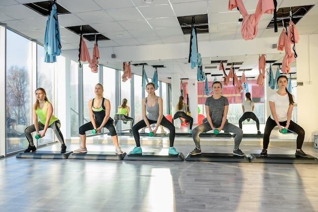 Grupo jovem e saudável de mulheres fazendo exercícios na academia