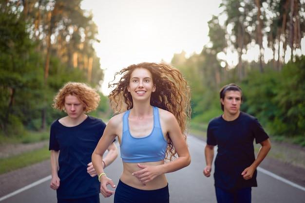 Grupo jovem homem e mulher caucasiano correndo estrada de asfalto manhã ensolarada de verão