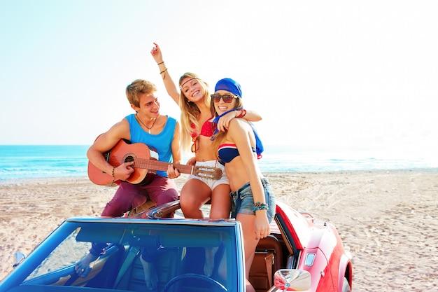 Grupo jovem se divertindo na praia tocando violão