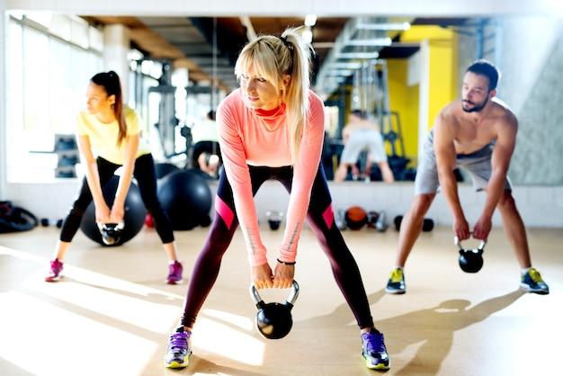 Grupo jovem tendo treinamento funcional fitness com um kettlebell no ginásio de esportes.