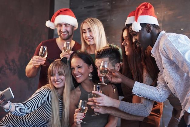 Grupo jovens bonitos fazendo selfie na festa de ano novo, melhores amigas meninas e meninos juntos se divertindo, posando de pessoas em estilo de vida emocional. chapéus de papai noel e taças de champanhe nas mãos