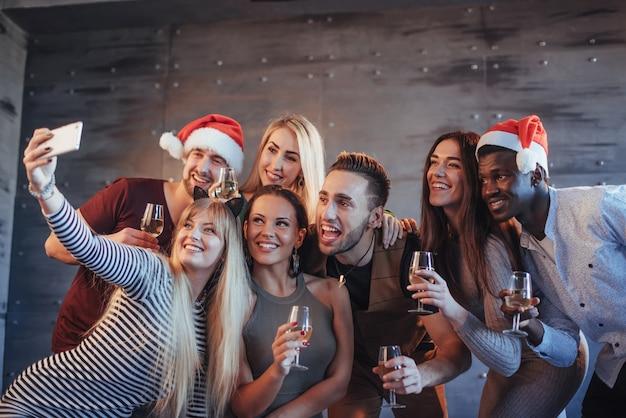 Grupo jovens bonitos fazendo selfie na festa de ano novo