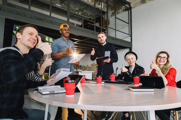 Grupo jovens empresários reunidos discutindo idéia criativa. grupo de estudantes internacionais, sentado à mesa com café e computadores e conversando