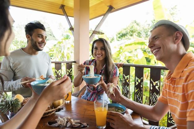 Grupo jovens, falando, enquanto, comendo macarronada sopa amigos tradicional, cozinha asiática, jantar, togeth