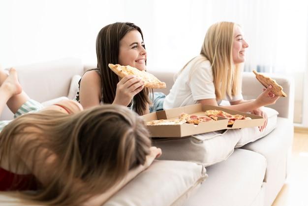 Grupo lateral de amigos comendo pizza
