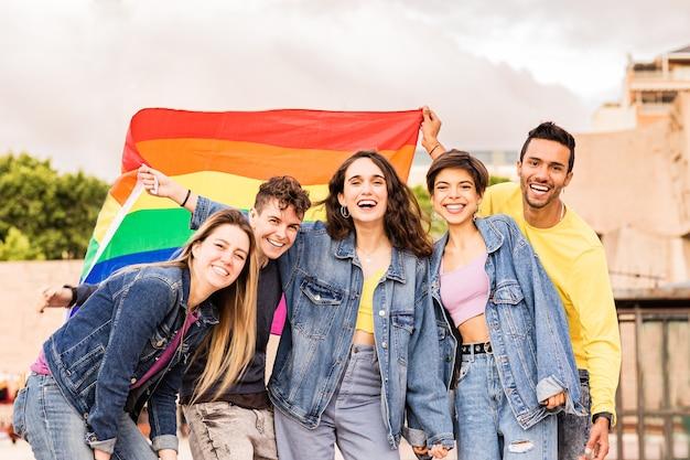 Grupo lgbtq de diversidade multiétnica com amigos bandeira do arco-íris para expressão de gênero e orgulho de identidade
