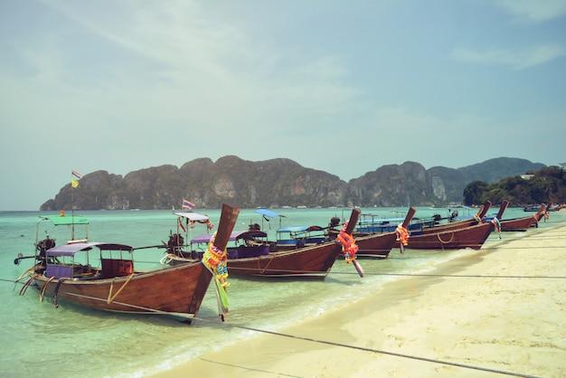 Grupo longo do barco na praia e no fundo brancos da montanha, phuket, tailândia