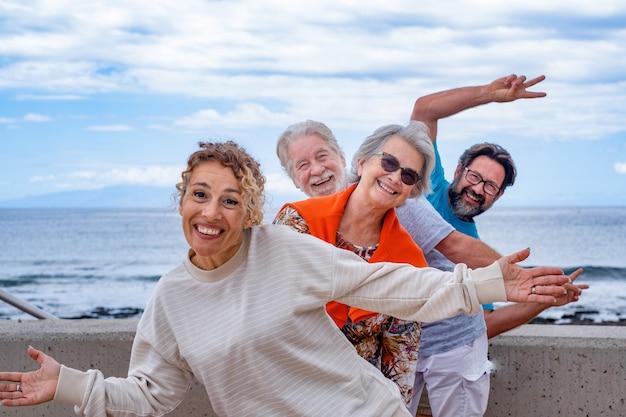 Grupo lúdico de família se divertindo juntos em excursão ao ar livre no mar sorrindo despreocupado