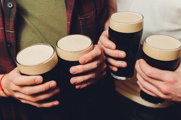 Grupo masculino, tilintar de copos de cerveja escura e clara na parede de tijolo