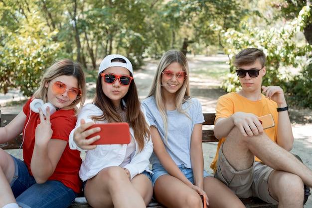 Grupo médio de amigos tirando selfie