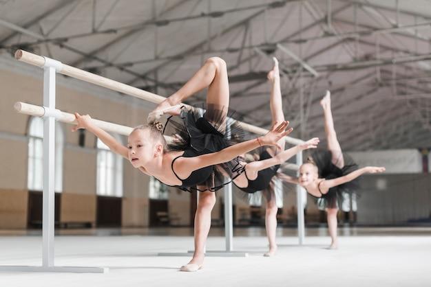 Grupo meninas, com, seu, perna, cima, perto, a, barre, durante, um, balé, classe