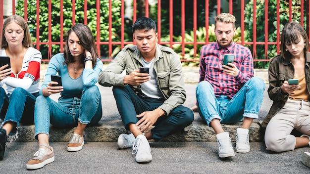 Grupo milenial de amigos usando smartphone sentado no quintal de uma faculdade universitária