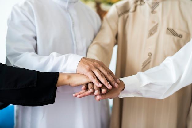 Grupo muçulmano de amigos empilhando as mãos