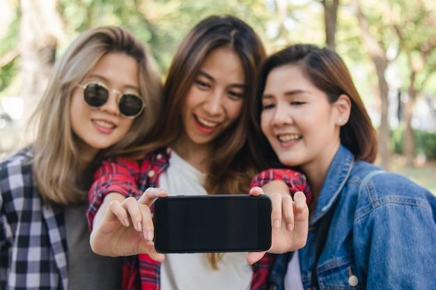Grupo mulheres asian, usando, smartphone, levando, selfie, enquanto, viajar, em, parque, em, urbano, cidade, em, bangkok