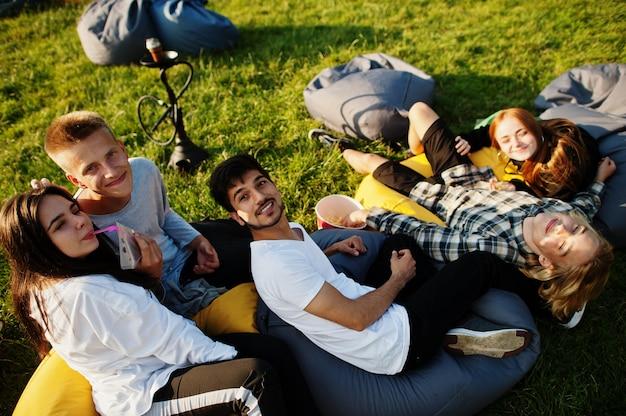 Grupo multi étnico jovem de pessoas assistindo filme em poof no cinema ao ar livre.