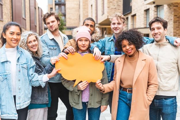 Grupo multicultural de amigos segurando um balão de pensamento laranja vazio
