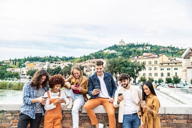 Grupo multicultural de amigos usando telefones celulares ao ar livre - alunos navegando na internet segurando telefones celulares inteligentes nas ruas da cidade - conceito sobre social, tecnologia, tendências tecnológicas e amizade