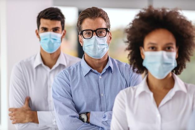 Grupo multicultural de empresários com máscaras em pé com os braços cruzados na empresa corporativa.