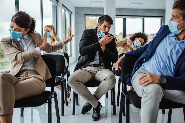 Grupo multicultural de empresários com máscaras, sentados em um seminário e defendendo o homem que está tossindo